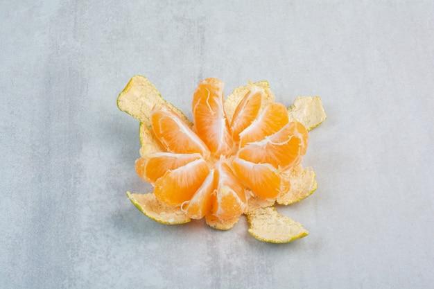 Peeled fresh tangerine on stone background