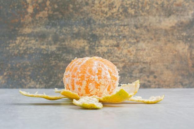 Mandarino fresco sbucciato sulla tavola di pietra. foto di alta qualità