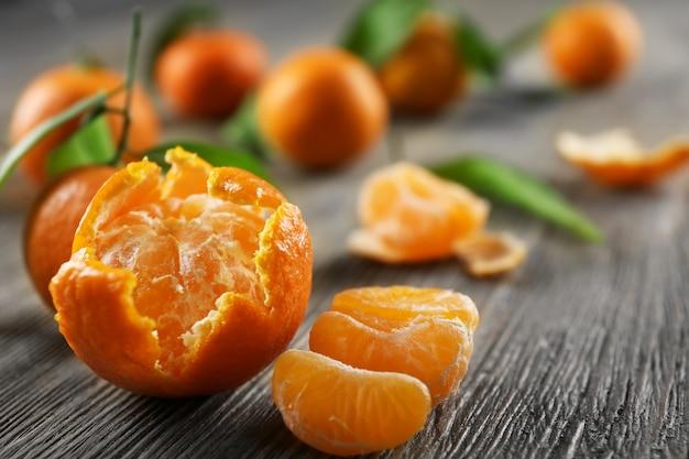 Очищенные свежие мандарины с листьями и спелыми мандаринами на деревянном столе, крупным планом