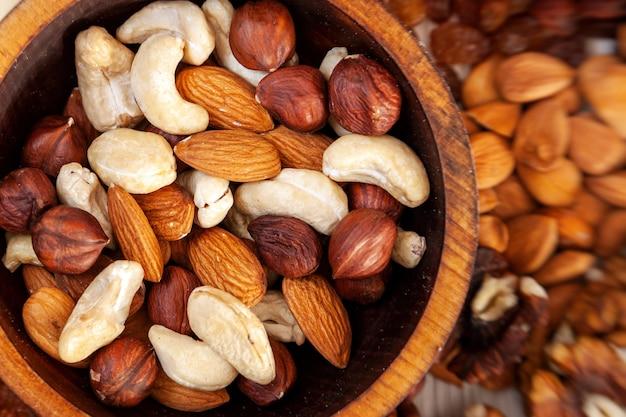 Очищенные фундук, кешью, миндаль в деревянной кедровой тарелке на фоне россыпи различных орехов. очищенный фундук, кешью