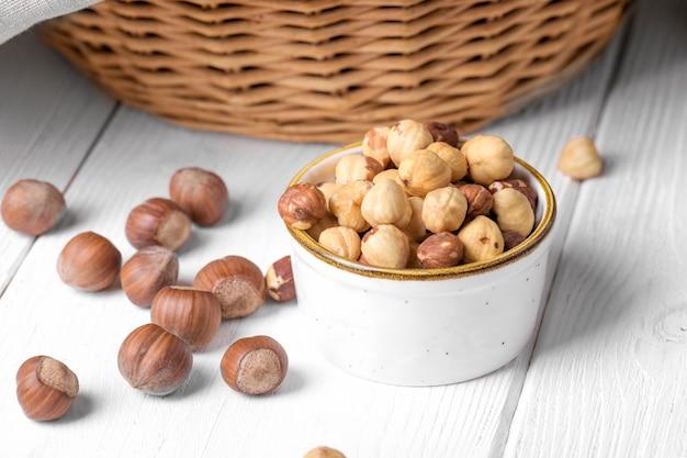 ボウルに皮をむいたヘーゼルナッツと白い木製の背景に全体のヘーゼルナッツ、クローズアップ。健康的なおやつと健康的な食事、秋の森の収穫