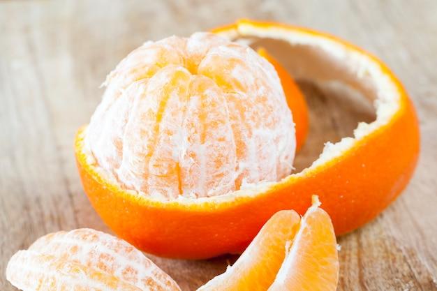 Peeled juicy fruit of mandarin with peel lying nearby, closeup