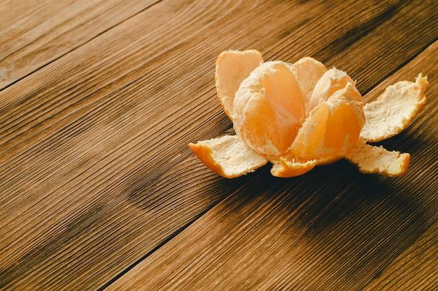 Peeled mandarin on a wooden table