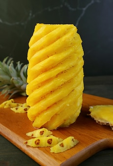 Peeled and nicely cut fresh ripe pineapple on a wooden cutting board