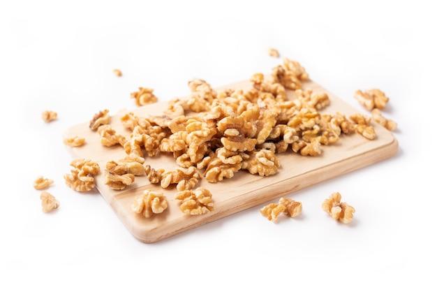 白の木製ボード上の皮をむいたナッツ