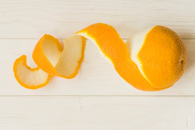 Peeled orange fruit on wooden background