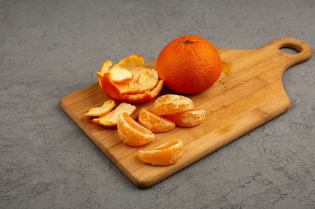 Peeled out tangerines along with whole and sliced fruit on a brown desk