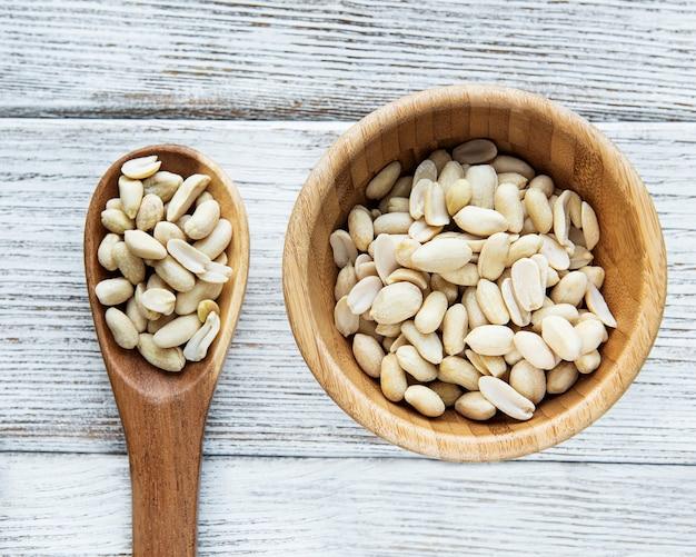 Очищенный арахис в деревянной миске на белой деревянной поверхности