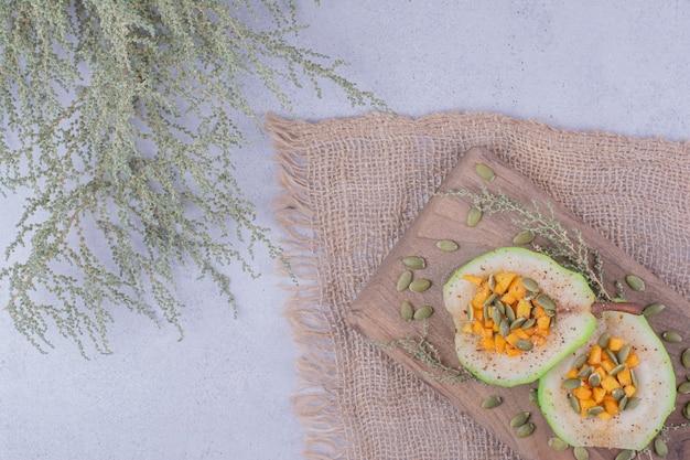 木の板ににんじんとかぼちゃの種を添えた皮をむいた洋ナシのサラダ