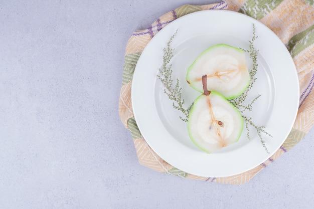 Pera sbucciata affettata con erbe in un piatto bianco.