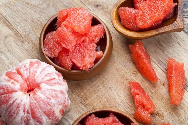 Очищенный розовый грейпфрут, разрезанный на кусочки во время приготовления, готов к употреблению сочный цитрусовый грейпфрут