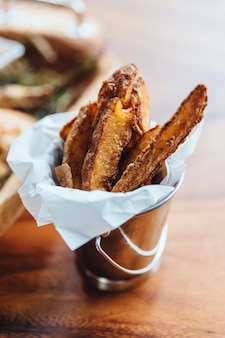 Peeled potato fries served in silver bucket as an appetizer or side dish.