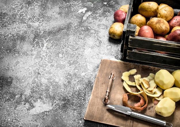 나무 보드에 껍질을 벗긴 감자. 소박한 배경.