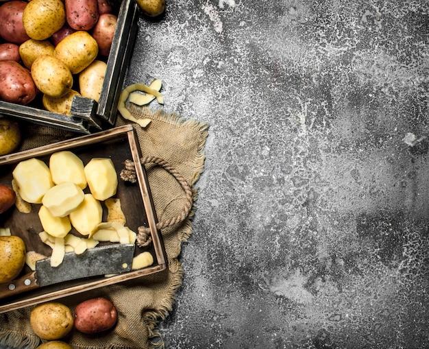 木の板に皮をむいたジャガイモ。素朴なテーブルの上。