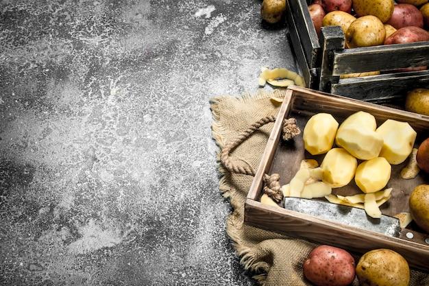 素朴なテーブルの木の板に皮をむいたジャガイモ。