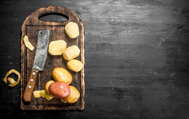 古いまな板の上でナイフでジャガイモを皮をむいた。