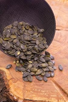 皮をむいたカボチャの種が暗いカップから木製にこぼれる