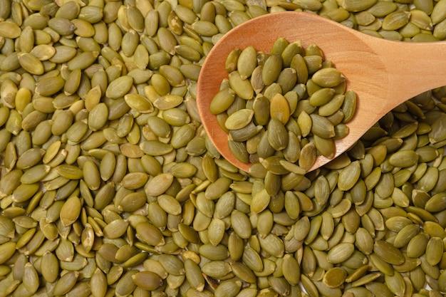 Очищенные семена тыквы. неочищенные ядра. орехи лежат в деревянной ложке.