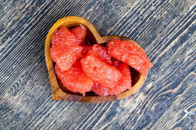 Очищенный красный грейпфрут, разделенный на дольки во время приготовления, сочный цитрусовый грейпфрут