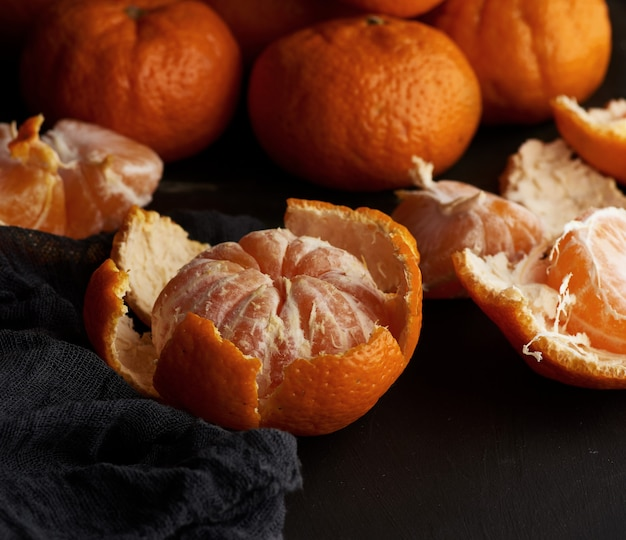 Peeled round ripe tangerines in a plate on a black textile napkin