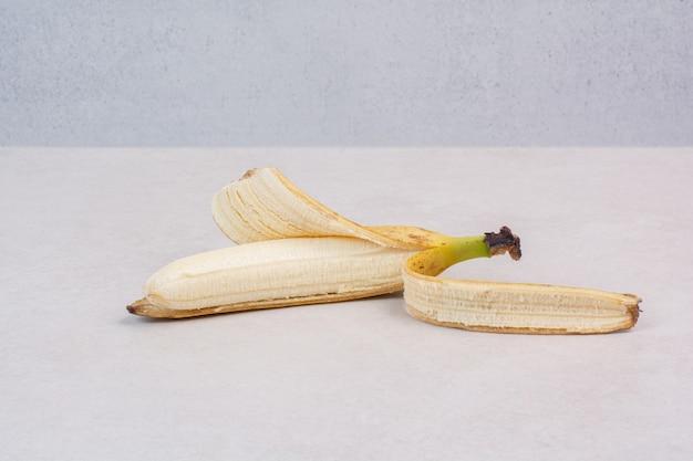 Очищенный одиночный банан на белом столе.