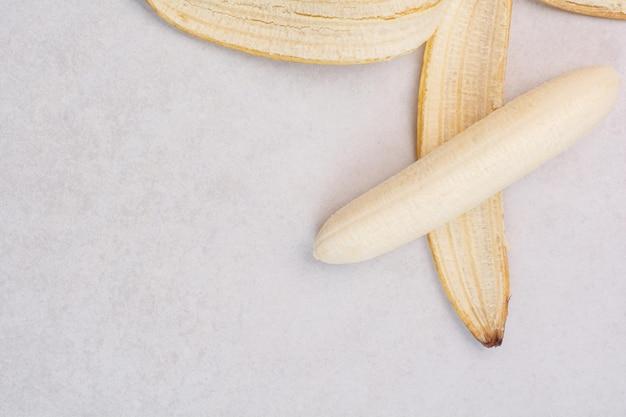 白いテーブルの上に皮をむいた単一のバナナ。