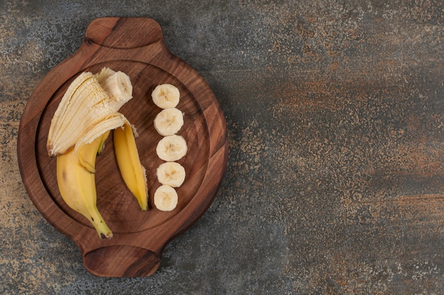 Peeled and sliced banana on wooden board