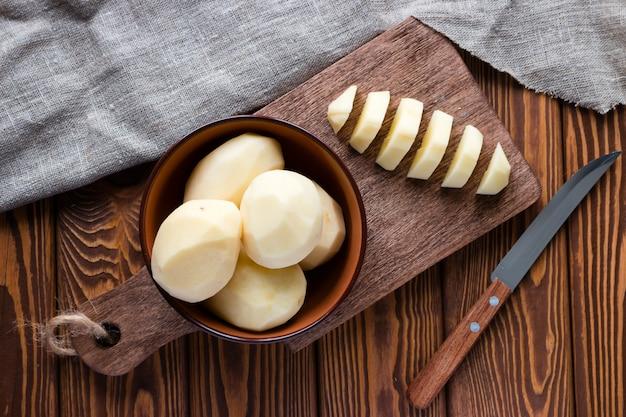 Peeled sliced potatoes on a cutting board