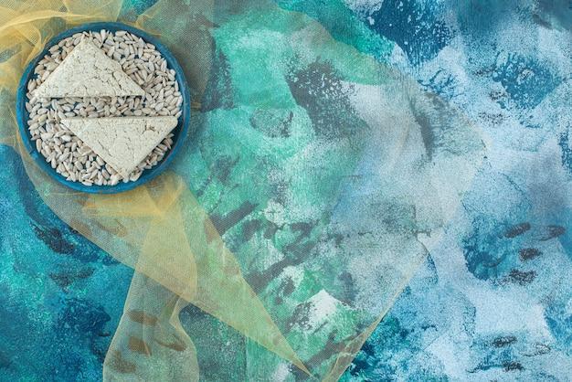 Очищенные семечки и нарезанная халва на деревянной тарелке на тюле, на синем столе.