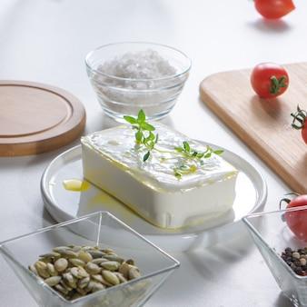 껍질을 벗긴 해바라기 씨앗, 치즈, 토마토 및 소금은 흰색 식탁에 미리 뿌려졌습니다. 단계별 건강 샐러드 요리 재료.