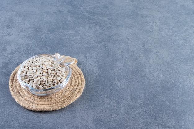 Semi di girasole pelati in una ciotola di vetro sul sottopentola, sullo sfondo di marmo.