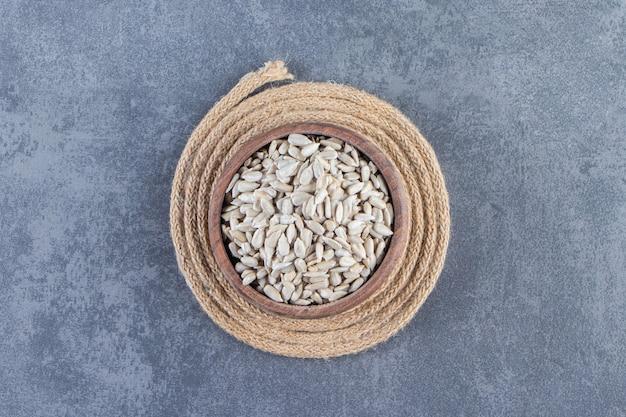 Очищенные семечки в миске на подставке на мраморной поверхности