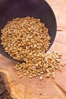 砂糖と蜂蜜で皮をむいたヒマワリの種、暗いカップから木製にこぼれる