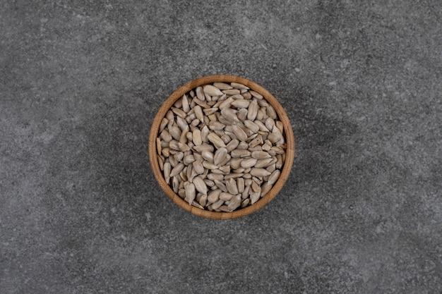 Semi di girasole sbucciati in ciotola di legno. vista dall'alto.