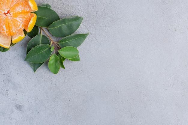 Очищенный мандарин и декоративные листья на мраморном фоне.
