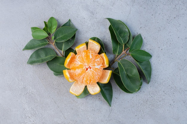 Peeled tangerine and decorative leaves on marble background.