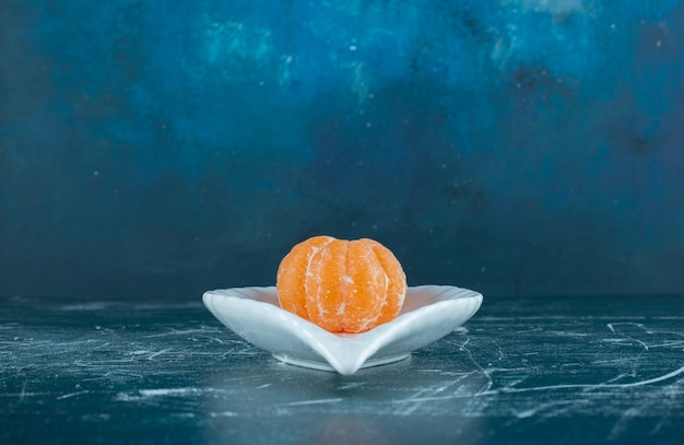 하얀 접시에 껍질을 벗 겨 귤 과일입니다.