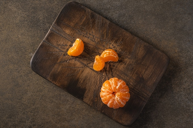 Peeled tangerine and slices on wooden textured board, copy space, top view