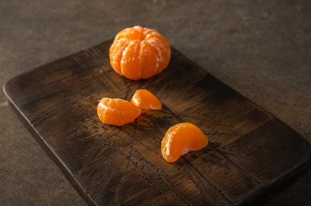 Peeled tangerine and slices on wooden textured board, selective focus, copy space