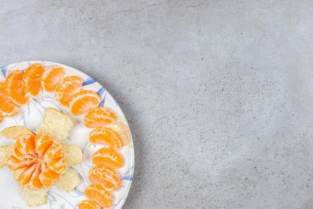 Mandarino sbucciato con fette di mandarino sulla piastra. primo piano foto.