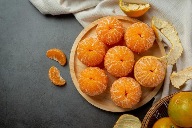 Peeled tangerines on old dark background