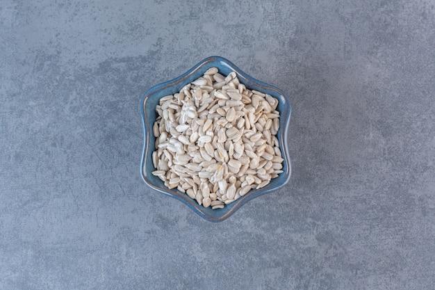 Semi di girasole sbucciati e saporiti in ciotola, sulla superficie di marmo