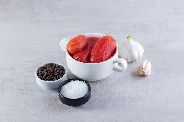 신선한 마늘과 향신료로 껍질을 벗긴 토마토를 돌 테이블에 놓습니다.