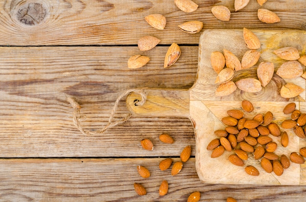 Peeled and unpeeled almonds on wooden board