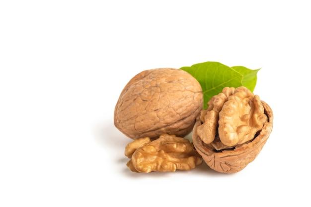Очищенные плоды грецкого ореха лежат на белом изолированном фоне с зелеными листьями грецкого ореха в оболочке белого изолята ...