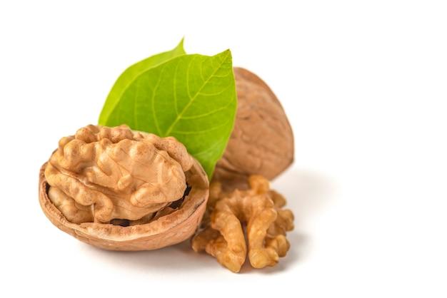 Очищенные плоды грецкого ореха лежат на белом изолированном фоне с зелеными листьями. грецкий орех в скорлупе. белый изолятор для дизайна и вставки в проект.