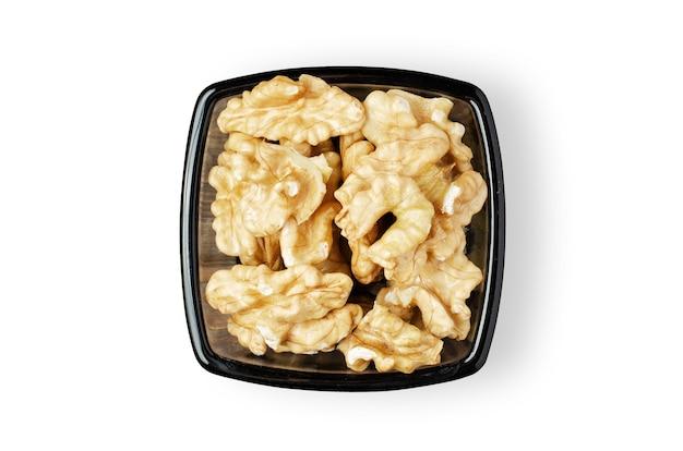 ボウルにクルミの実をはがしました。白い背景で隔離。ナッツには植物性タンパク質とビタミンが含まれています。健康的で菜食主義の食事のために。