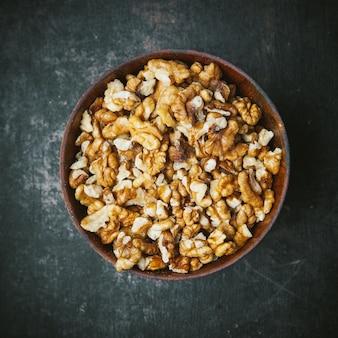 Очищенные грецкие орехи в коричневой миске на темном столе