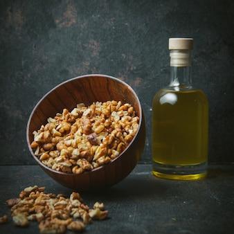 Очищенные грецкие орехи в коричневой миске с маслом грецкого ореха в стеклянной бутылке сбоку на темном столе