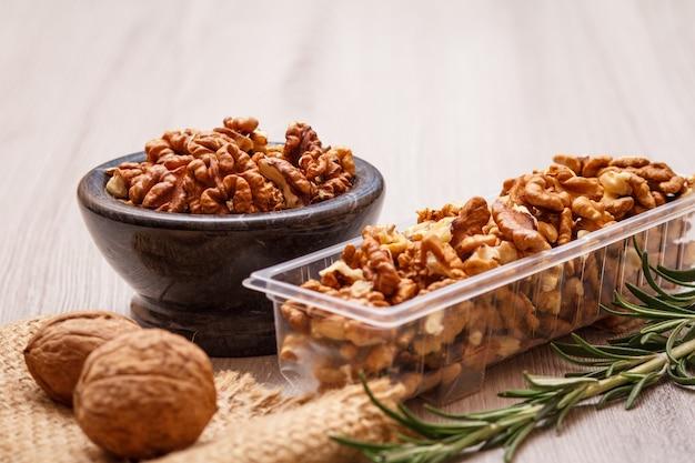 돌 그릇에 껍질을 벗긴 호두와 로즈마리가 든 자루천에 껍질을 벗기지 않은 것이 들어 있는 플라스틱 용기. 유용한 영양가 있는 단백질 제품. 필드의 얕은 깊이.